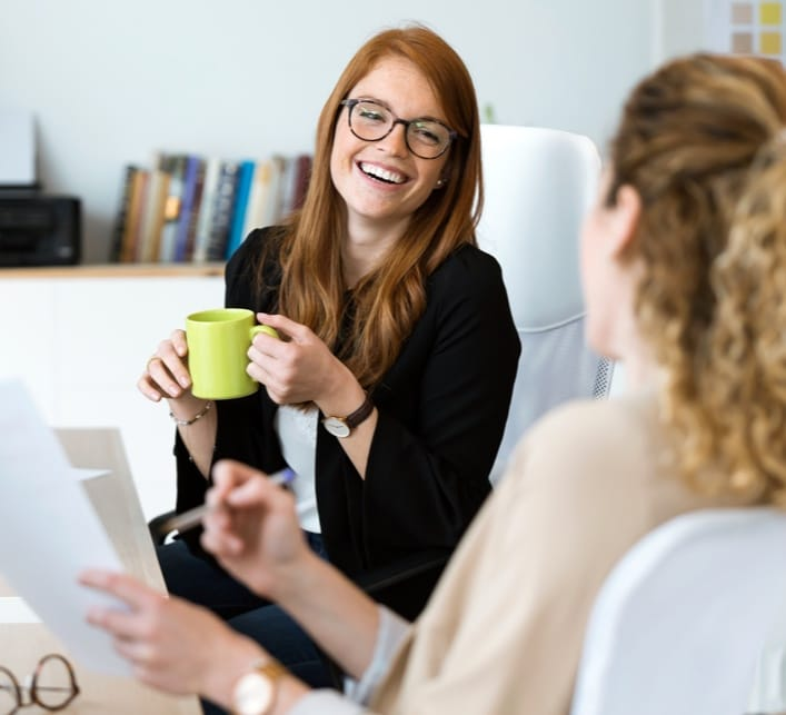Woman holding a coffee cup talking with someone else